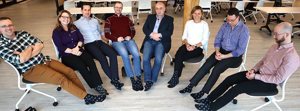 People sitting with PEER Group-branded socks on