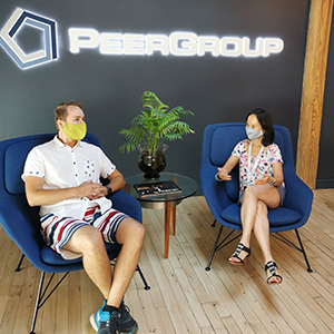 Two people chatting with masks on at PEER Group