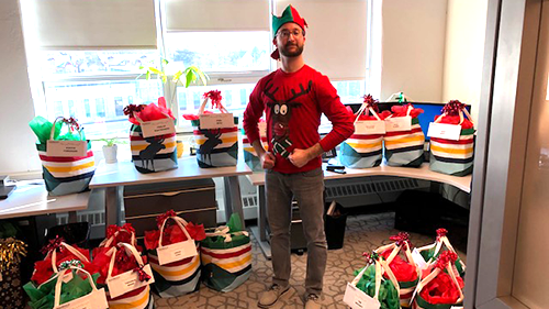"""Elf"" employee ready to give Christmas gifts in the office"