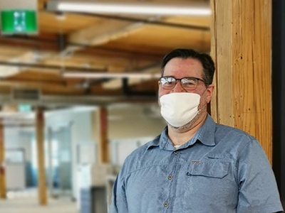 Man smiling with a mask on in the office